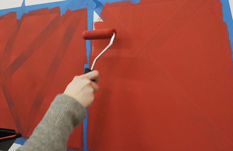 Use a Mini Roller with and emulsion sleeve to paint over the wall and the tape.